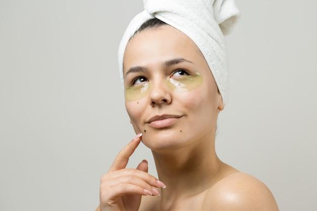 Молодая красивая девушка в белом полотенце на голове носит коллагеновые гелевые пластыри под глазами
