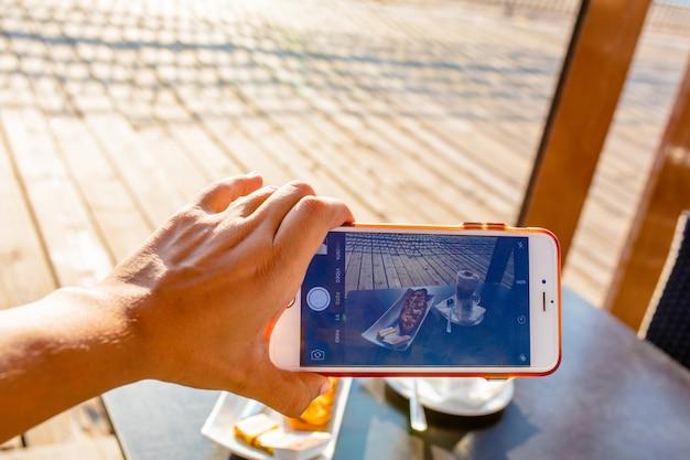 携帯電話で古典的なスペインの朝食を撮る