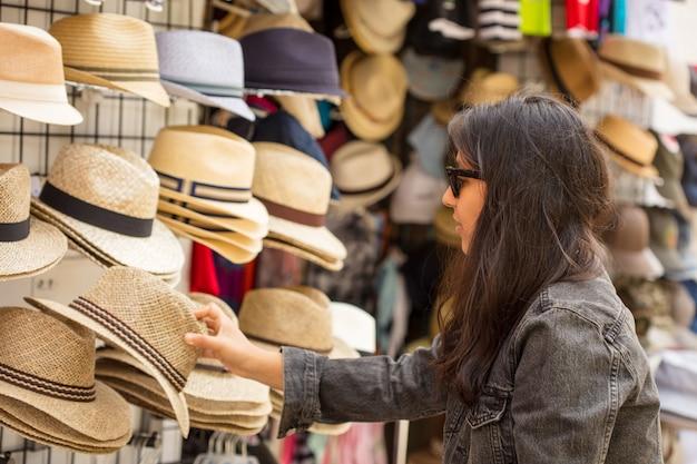帽子を買う若いインド人女性