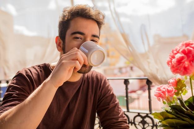 若い男がコーヒーを飲む