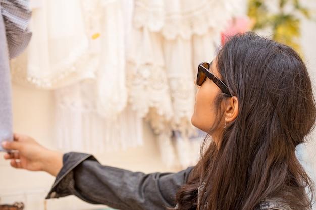 Молодая женщина покупает одежду
