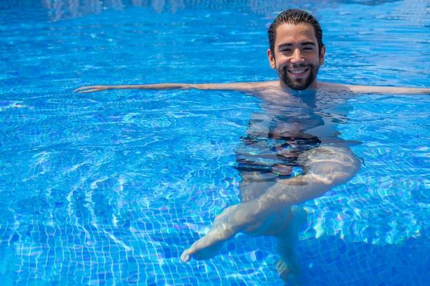 若い男がプールでリラックス