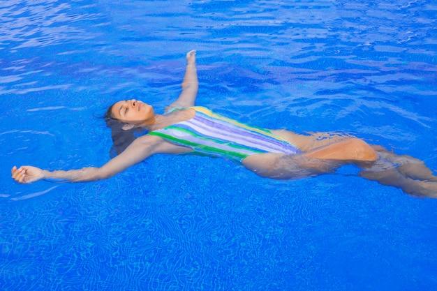 プールに浮かぶ若い女性