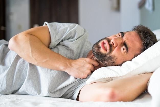 喉の痛みを持っているベッドで若い男
