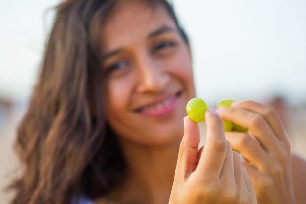 ビーチで果物を食べる若い女性