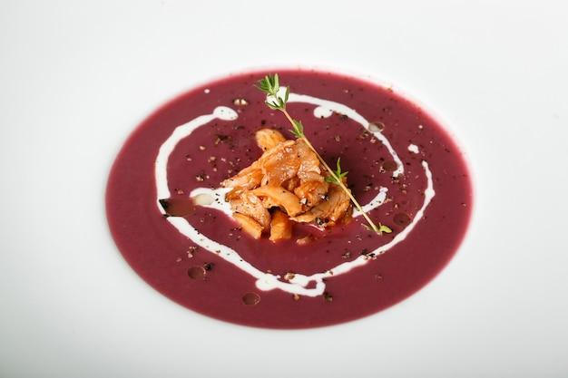 イカ料理と赤いクリームスープのクローズアップ
