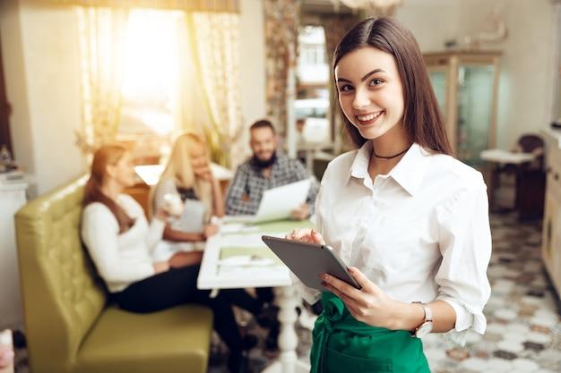 Официантка портрета усмехаясь молодая стоя в кафе