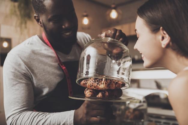 男性のバリスタは女の子がデザートを選ぶのを助けます