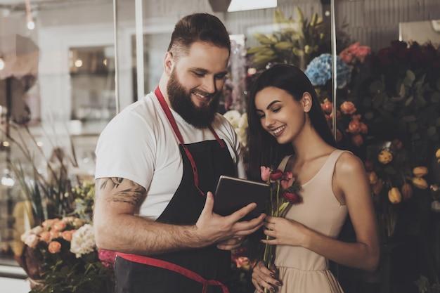 Бородатый мужчина и красивая девушка смотрят планшет