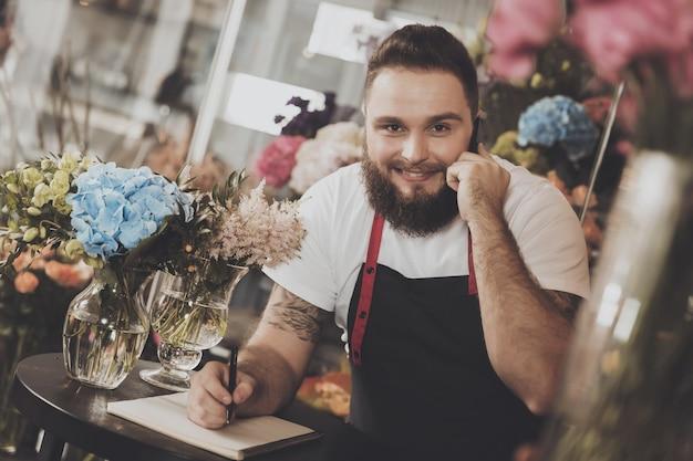 ひげを生やした花屋は携帯電話で注文を取ります
