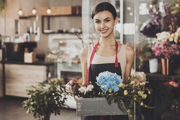 フラワーショップで美しい少女の花屋の肖像画