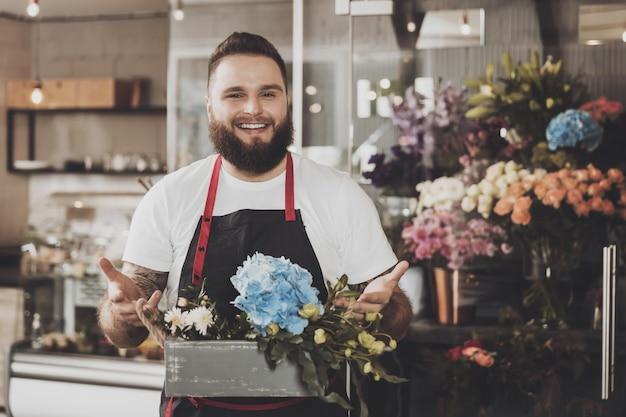 花束を持つひげを生やした男の花屋の肖像画