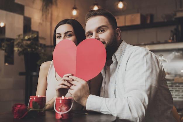 若い魅力的なカップルは紙のハートの後ろに隠れます