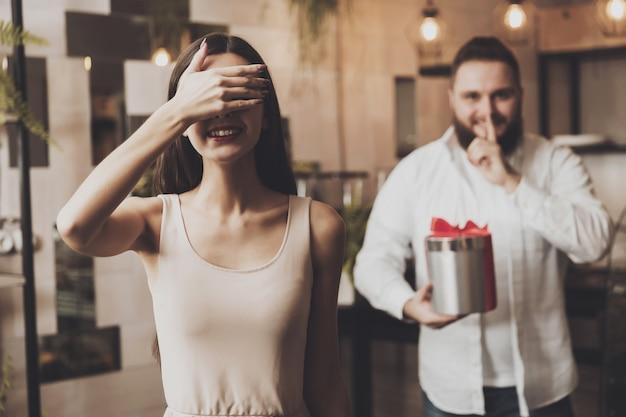 Мужчина дарит подарок девушке с закрытыми глазами