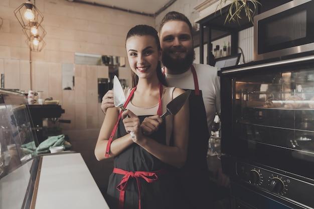 Два профессиональных пекаря стоят возле духовки.
