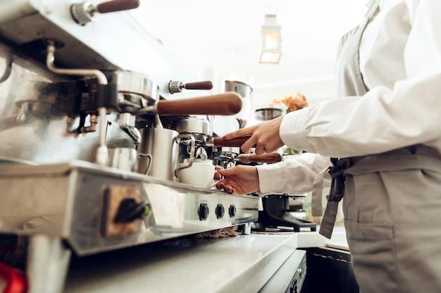 コーヒーを準備する女性のバリスタのクローズアップ