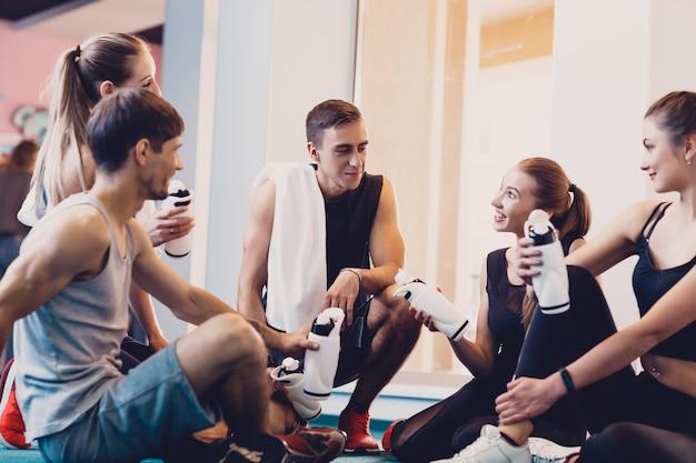 トレーニングの後に休んでいる幸せな人々のグループ。