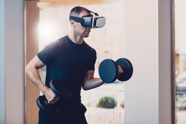 Человек в очках виртуальной реальности с гантелями