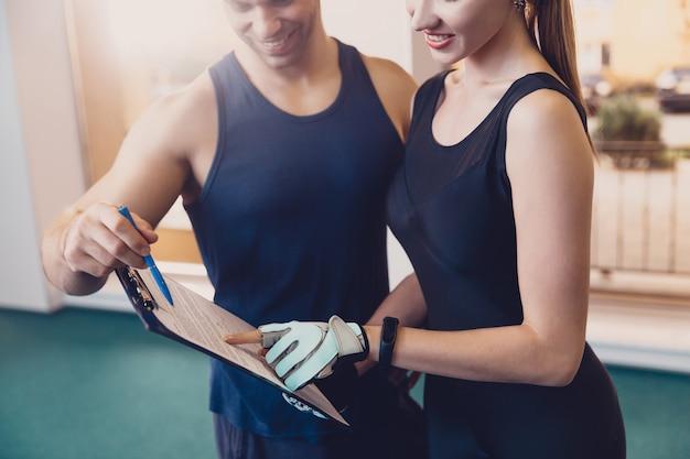 トレーナーは、女の子をトレーニングするフィットネスプログラムを書きます