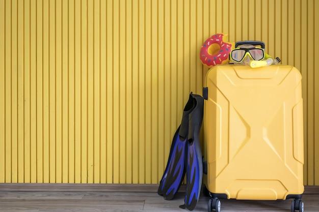 黄色のスーツケースと旅行者のダイビング用品