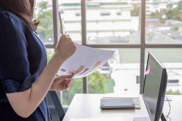 オフィスの女性は、ドキュメントファイルを見て立っています。