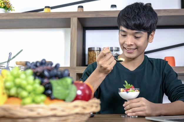 ハンサムな若い男性はフルーツヨーグルトを食べて幸せです。
