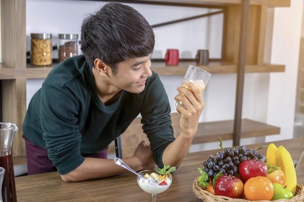 ハンサムな若い男はミルクティーを飲んで幸せです