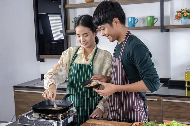 若い男と美しいアジアのティーンエイジャーは、モダンなキッチンでエビのサラダを作って喜んでいます。
