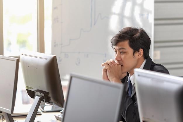 若いビジネスマンはオフィスの机で強調されています