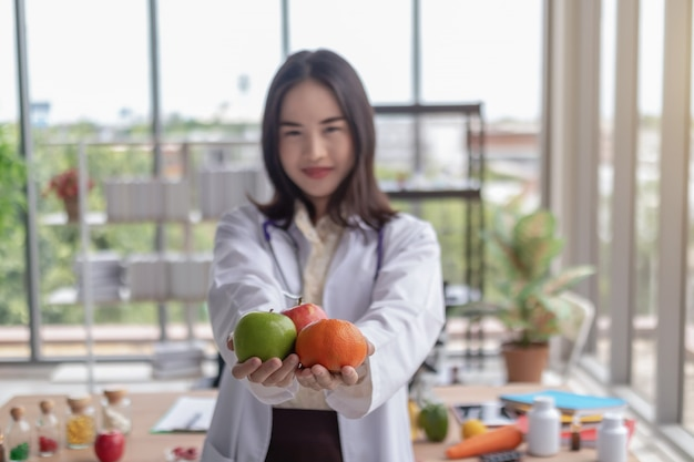 美しい医者はオフィスで果物を見せています。
