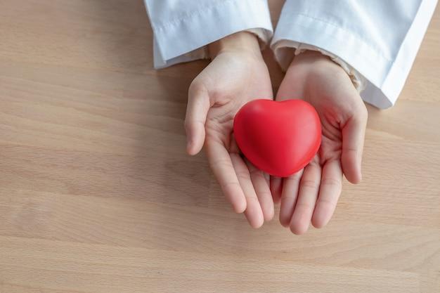 Крупный план красных сердец в руках женщин