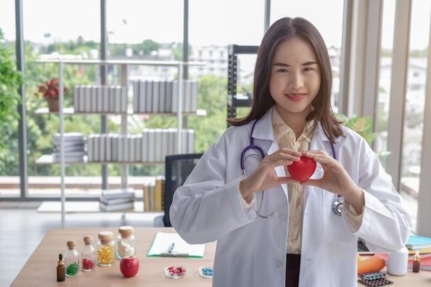 医者はオフィスで赤いハートを見せています