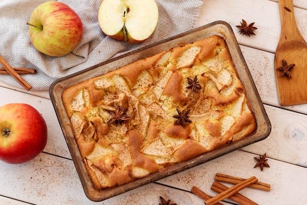 木製の背景にシナモンとアップルパイ