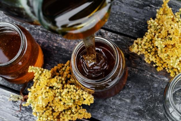 Свежий мед в стеклянной банке на деревянных фоне.