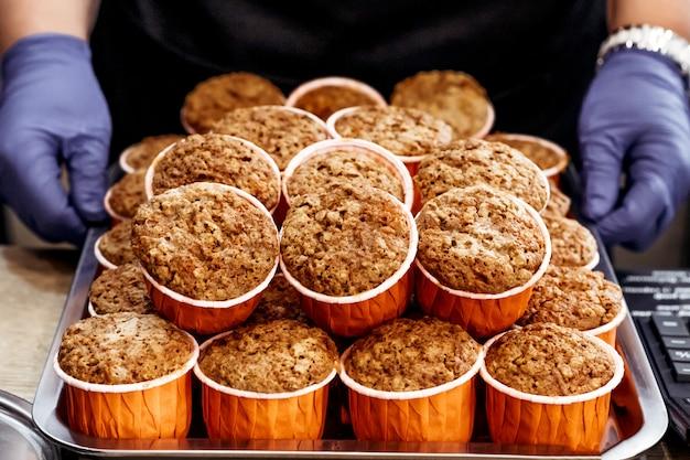 カボチャとニンジンのカップケーキ。健康的な秋のペストリー。カフェのコンセプト。パティシエの手で焼く。