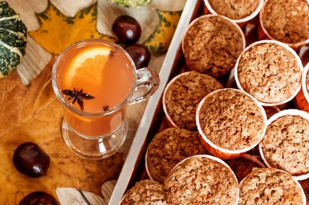 カボチャとニンジンのカップケーキとオレンジ色の秋の飲み物。健康的な秋のペストリー。カフェのコンセプト、メニュー。