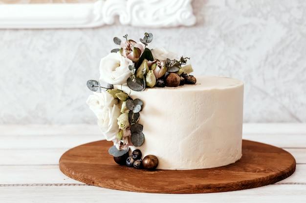 Белый свадебный торт украшен цветами эустомы и эвкалипта. место для текста.