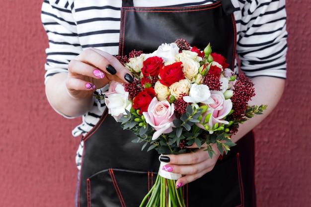 バラのウェディングブーケを持って若い花屋。さまざまな花のファッションモダンなブーケ。