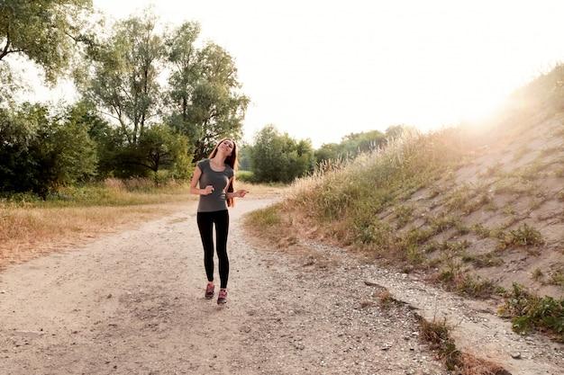 Девушка с длинными волосами бегает на закате на открытом воздухе. концепция спорта, здорового образа жизни, ухода за телом.
