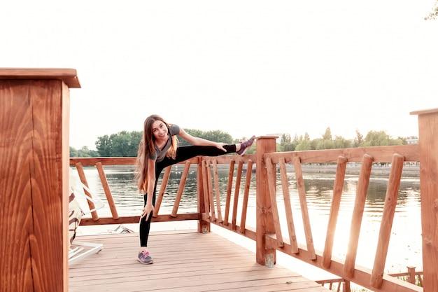 Девушка делает упражнения на пляже рано утром ... концепция спорта, здорового образа жизни, ухода за телом.