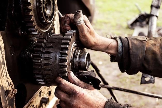 男はトラクター、農業機械のエンジンを修理します。ベアリング、ギア、クローズアップ。