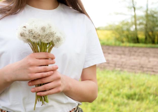 夕暮れ時の夏の庭のタンポポの花束と長い髪の茶色の髪の少女。テキストのための場所。