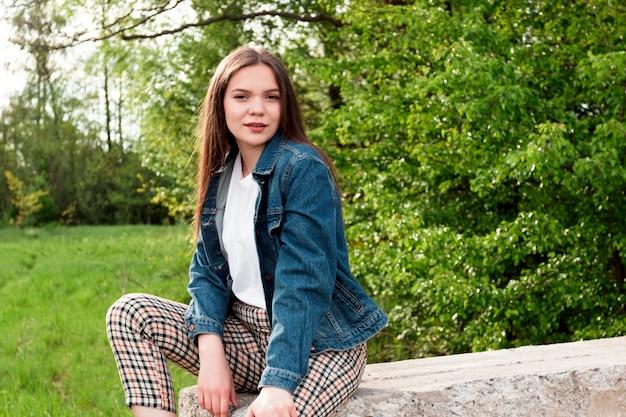 Маленькая девочка с длинными коричневыми волосами сидит на камне в зеленом лете, лесе весны.