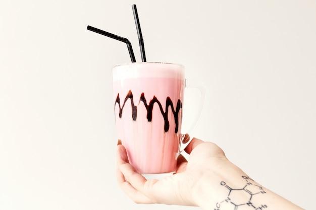Холодный розовый молочный коктейль в стеклянной кружке. коктейль держит руку женской татуировки. минимализм.