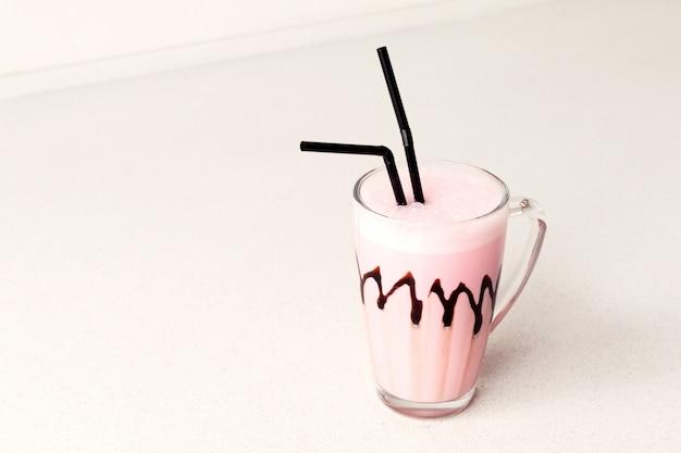 Холодный розовый молочный коктейль в стеклянной кружке. место для текста.