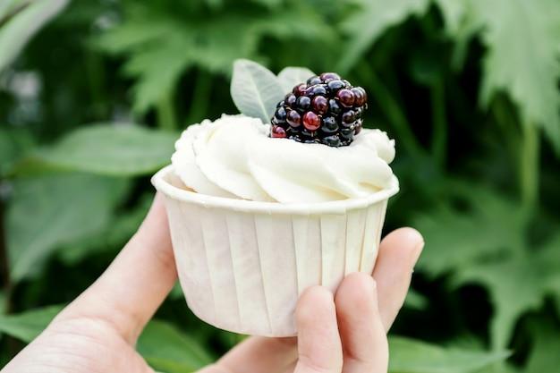 女の子は、ホイップクリームとブラックベリーのカップケーキを手で保持しています。緑の背景の食品ミニマリズム。