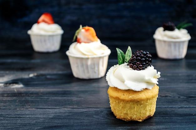 ホイップクリームとイチゴ、古い青い背景にブラックベリーのカップケーキ。