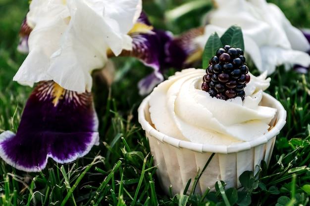 ホイップクリームと緑の芝生にブラックベリーのカップケーキ。