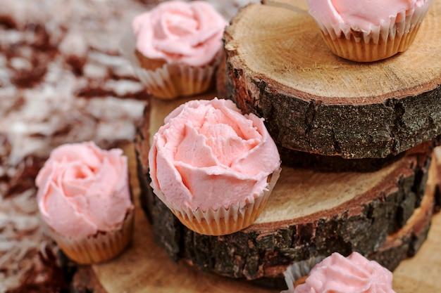 木製の背景にピンクのクリームのカップケーキ。