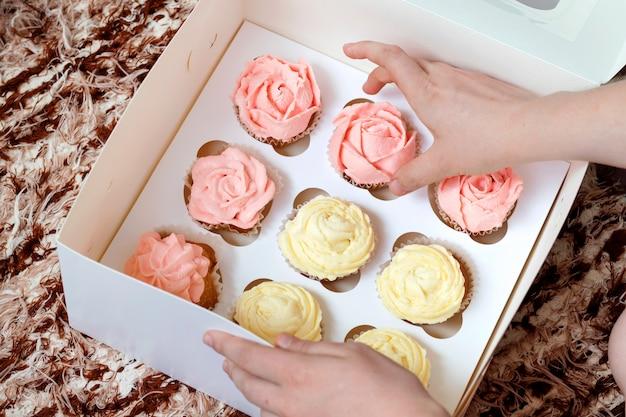 茶色の背景に紙箱にピンクと黄色のクリームのカップケーキ。